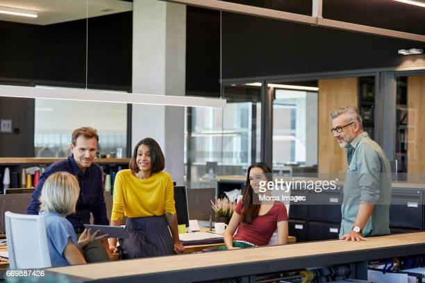 Businesswoman showing tablet PC to coworkers in office