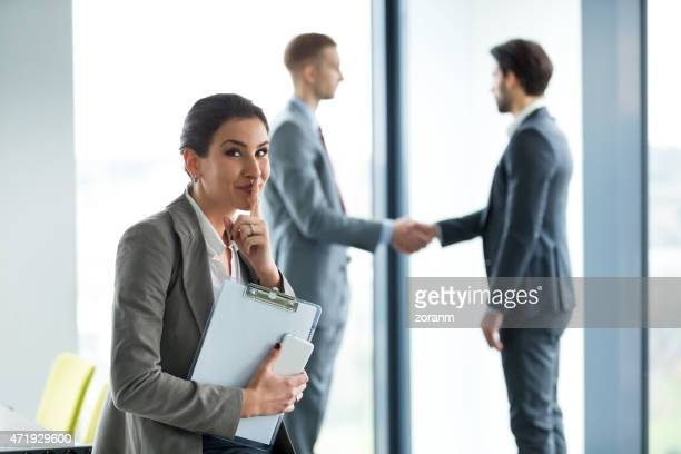 Businesswoman shushes with a smile as two men shake hands