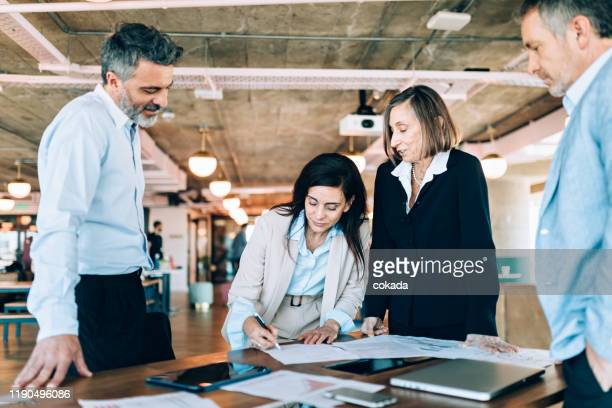 businesswoman signing contract document - contract stock pictures, royalty-free photos & images