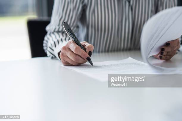 Businesswoman signing document at desk in office