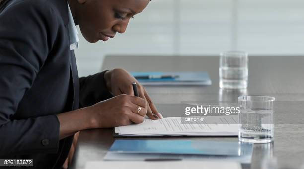 businesswoman signing document - blue blazer stock pictures, royalty-free photos & images