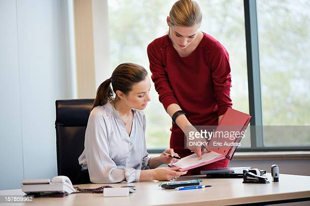 businesswoman signing documents with her secretary - secretary stock photos and pictures