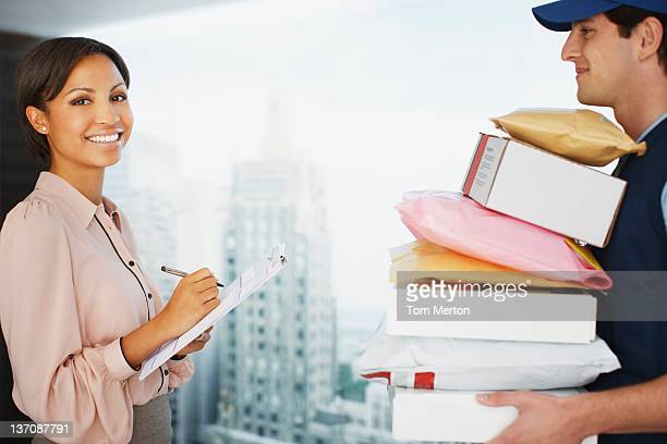 Businesswoman signing for packages in office