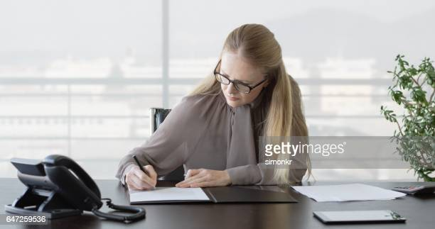 Businesswoman signing on document