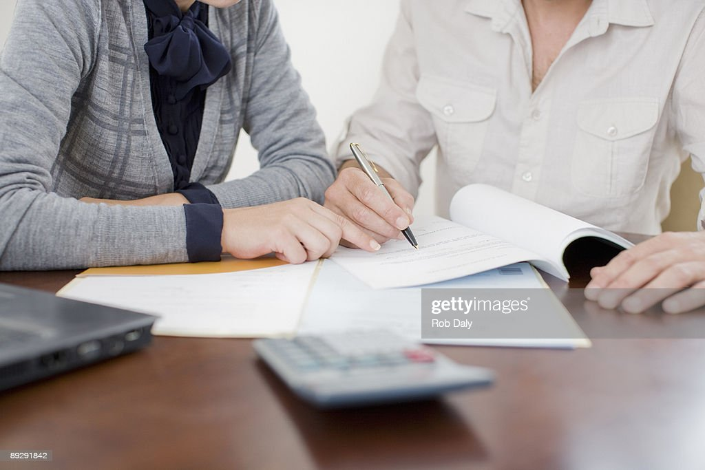 Businesswoman signing paperwork : Stock Photo