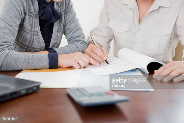 businesswoman signing paperwork - mortgage stock pictures, royalty-free photos & images