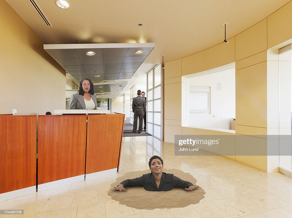 Businesswoman Sinking In Office Quicksand : Foto de stock