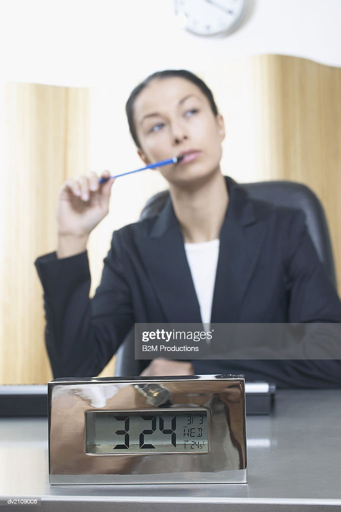Businesswoman Sits at a Desk Thinking, Focus on Alarm Clock : Stock Photo