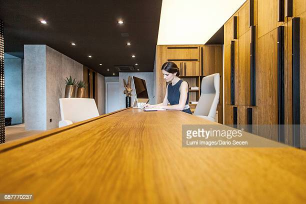 Businesswoman sits at conference table using computer