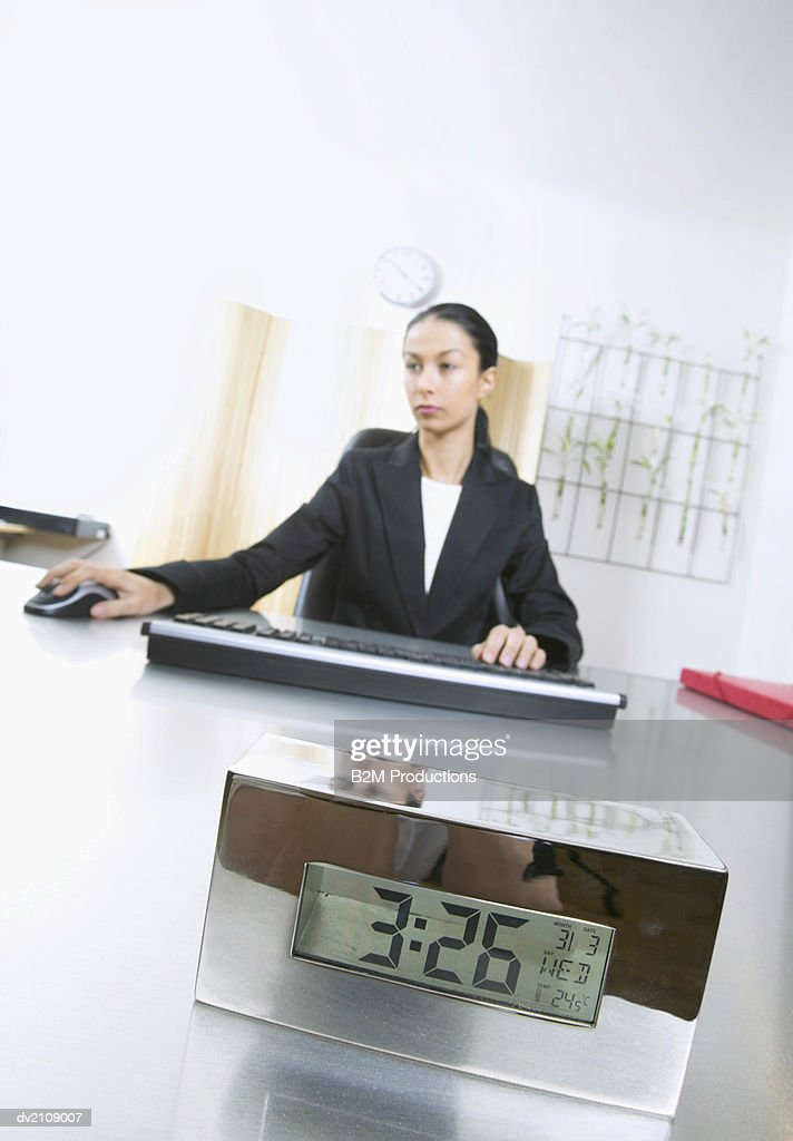 Businesswoman Sits at Desk With an Alarm Clock on it Using a Computer Mouse : Stock Photo