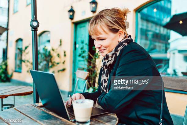 Businesswoman sits at outdoor cafe using her laptop computer