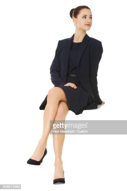 businesswoman sitting against white background - sitting foto e immagini stock