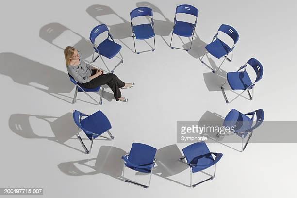 businesswoman sitting alone in circle of chairs, elevated view - cadeira dobrável - fotografias e filmes do acervo