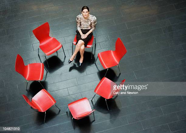 Businesswoman sitting alone in circle of chairs