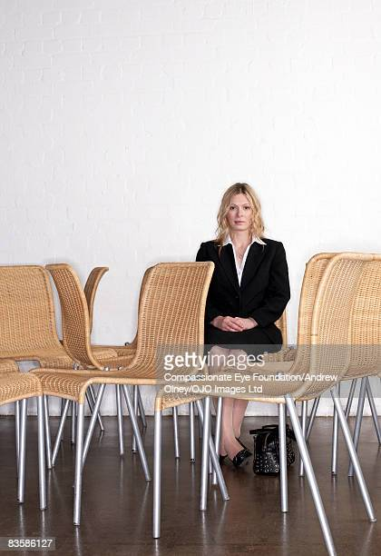 businesswoman sitting amongst empty chairs - cef stock pictures, royalty-free photos & images