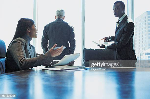 Businesswoman Sitting at a Conference Room Table and Arguing With a Businessman Pointing to a Document