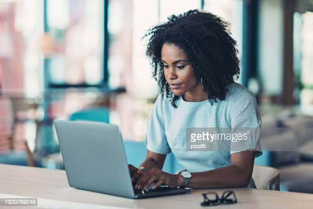 businesswoman sitting at a desk and typing on a laptop - audience free event stock pictures, royalty-free photos & images