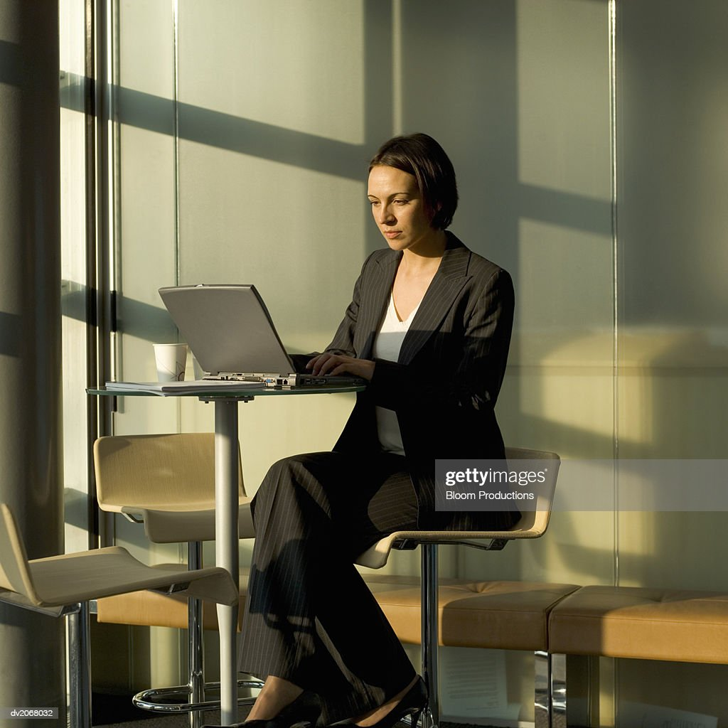 Businesswoman Sitting at a Table Using a Laptop : Stock Photo