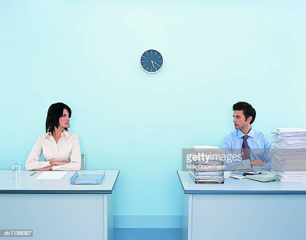 Businesswoman Sitting at a Tidy Desk Looking Sideways at a Businessman Sitting at a Messy Desk