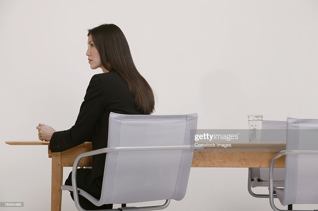 Businesswoman sitting at conference table : Stockfoto