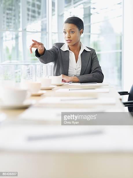 ビジネスウーマンのコンファレンステーブルに座る