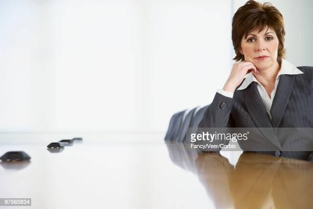 businesswoman sitting at conference table - surexposition effet visuel photos et images de collection