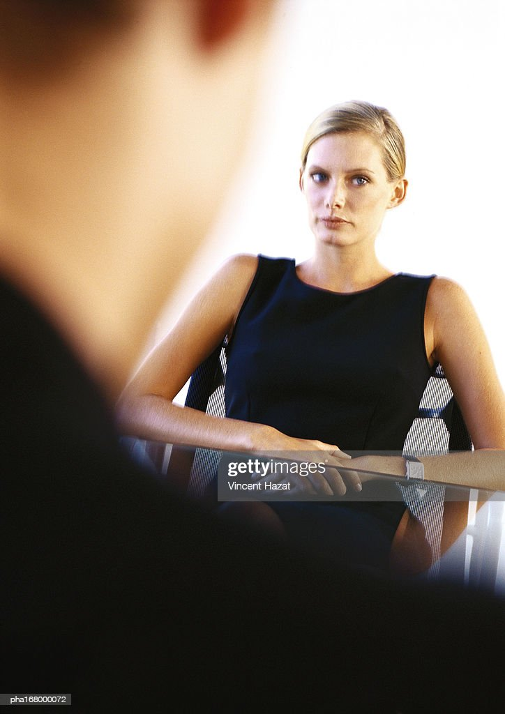 Businesswoman sitting at desk, blurred : Stock Photo
