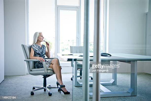 businesswoman sitting at desk contemplating - businesswear stock pictures, royalty-free photos & images