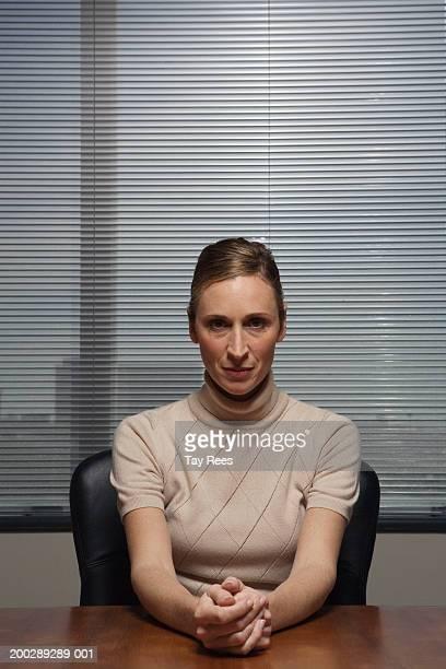 Businesswoman sitting at desk, hands clasped, portrait