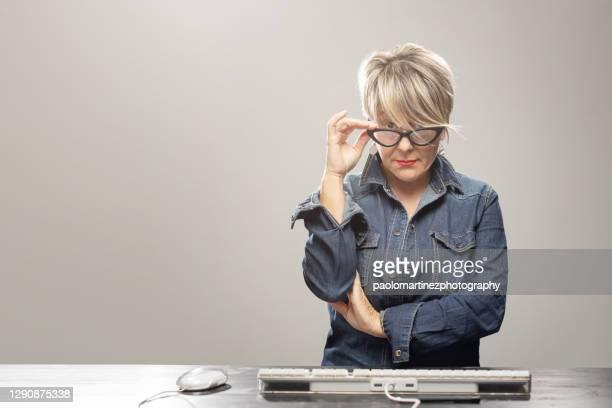 businesswoman sitting at desk holding eyeglasses - straffen stockfoto's en -beelden