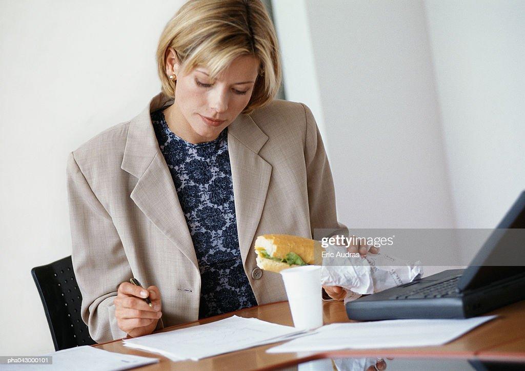 Businesswoman sitting at desk, holding sandwich : Stockfoto