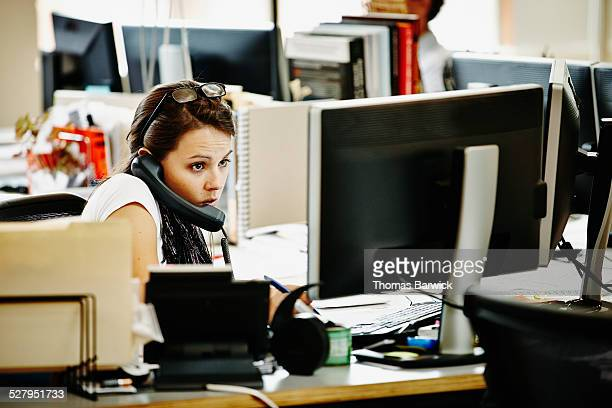 Businesswoman sitting at desk in office on phone