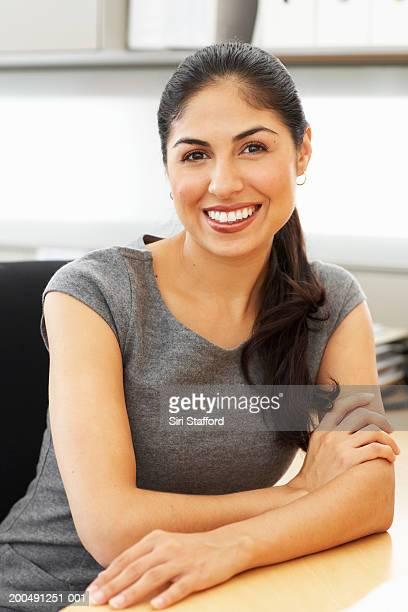 Businesswoman sitting at desk in office, portrait