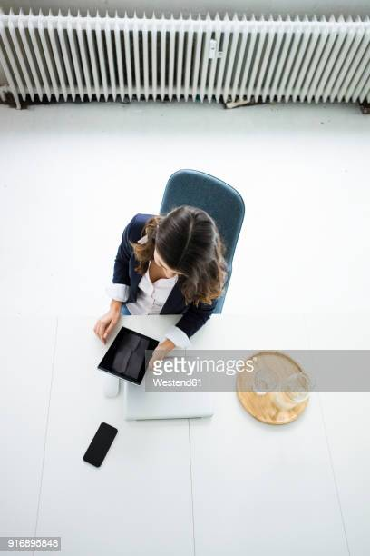 Businesswoman sitting at desk in the office working on tablet, top view