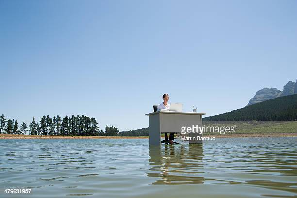 businesswoman sitting at desk in water with laptop - out of context stock pictures, royalty-free photos & images