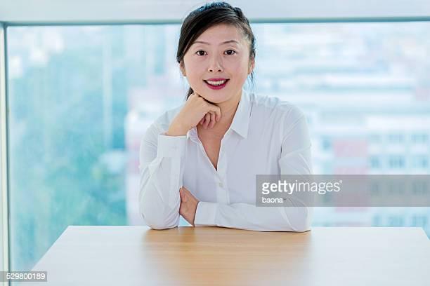 デスクでのビジネスウーマンのラウンジ - 顎に手をやる ストックフォトと画像