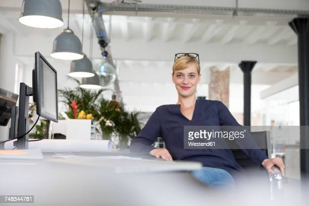 businesswoman sitting at desk - gelassene person stock-fotos und bilder