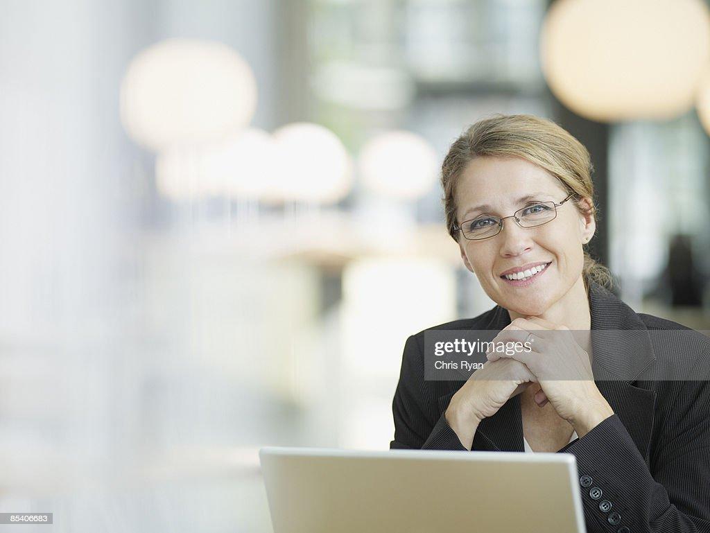 Businesswoman sitting at desk : Stock Photo