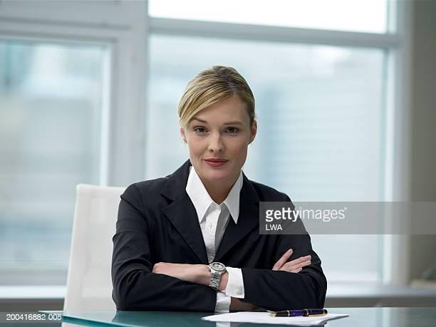 Businesswoman sitting at desk, portrait, close-up