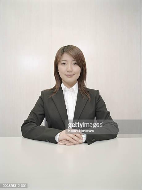 Businesswoman sitting at desk, portrait