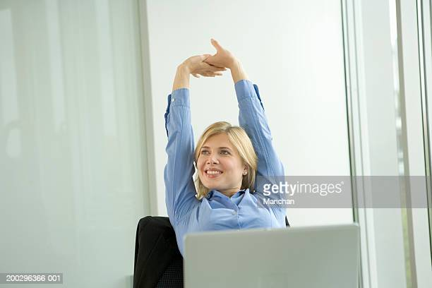 Businesswoman sitting at desk stretching arms up, smiling