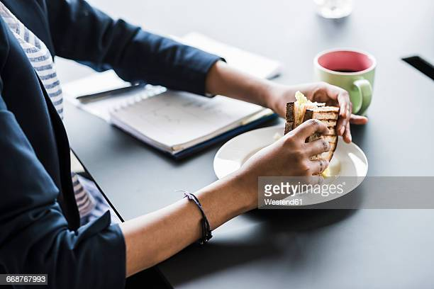 Businesswoman sitting at desk taking sandwich, partial view
