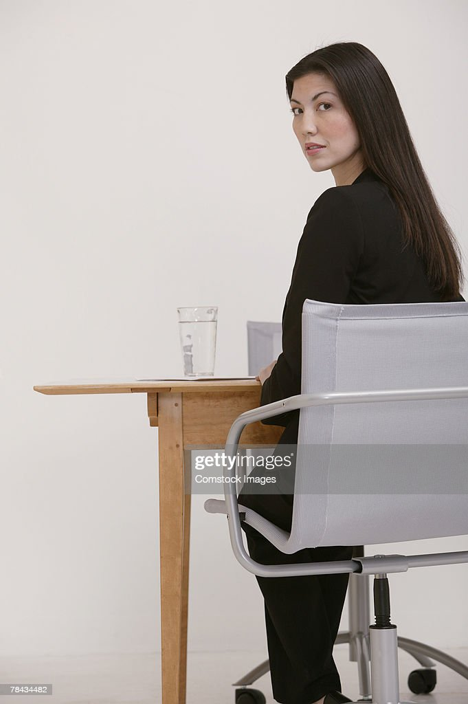 Businesswoman sitting at desk , turning around : Stockfoto