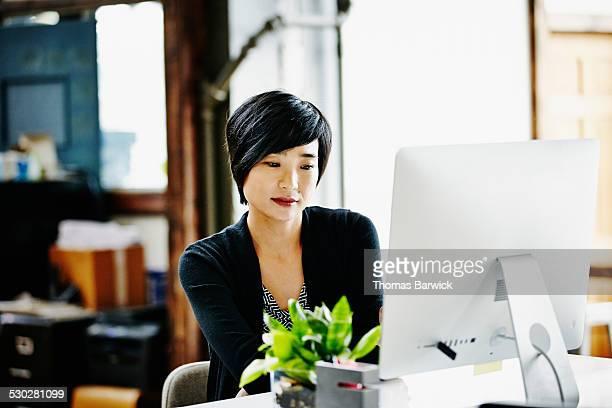 Businesswoman sitting at desk working on computer