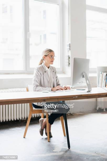 Businesswoman sitting at desk working with computer