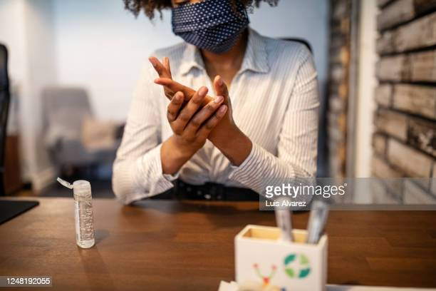 businesswoman sitting at her desk cleaning hands with sanitizer - hygiene stock pictures, royalty-free photos & images