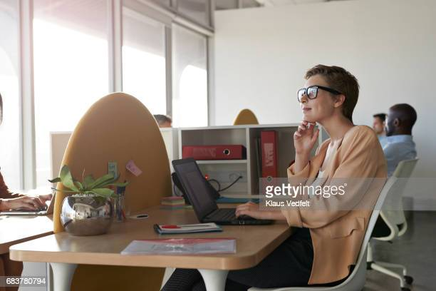 Businesswoman sitting at office desk, looking out of window