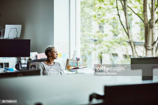 businesswoman sitting at office workstation looking out window - selective focus photos et images de collection