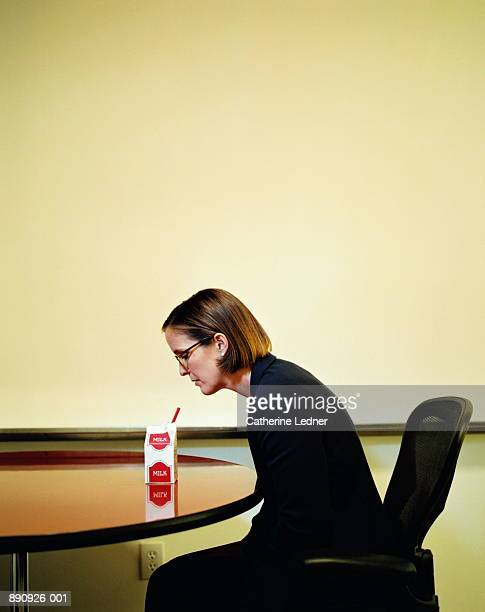 businesswoman sitting at table with small carton of milk - carton stock photos and pictures