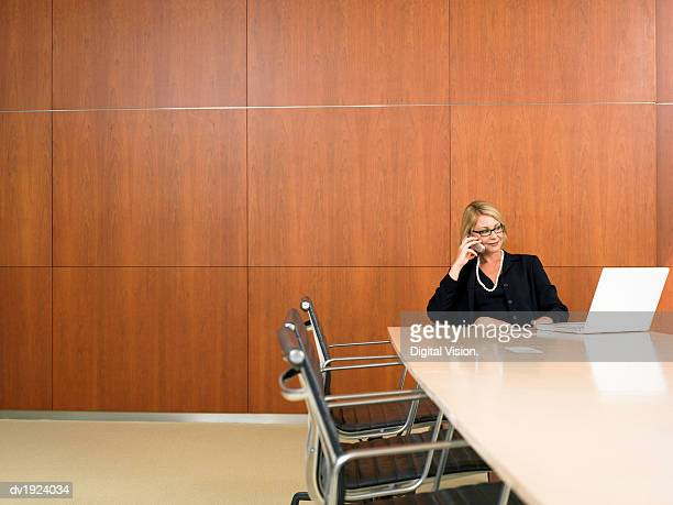 Businesswoman Sitting at the End of a Conference Room Table Using Her Mobile Phone